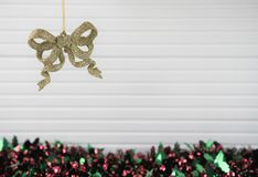 Christmas photography image of xmas decoration hanging up gold glitter bow bauble with tinsel and white wood background Royalty Free Stock Photos