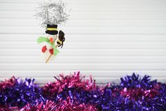 Christmas photography image of xmas decoration hanging up hand made snowman purple tinsel and white wood background Royalty Free Stock Photo