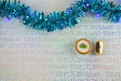 Christmas photography image of xmas food mince pies with blue tinsel and light wrapping paper background Stock Photos