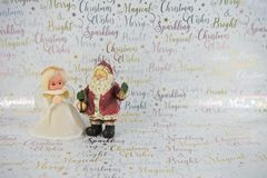 Christmas photography of old vintage hand made white gold fairy tree topper and Santa Claus on xmas wrapping paper background Stock Photo