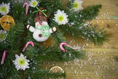 Christmas photography picture with tree branches and cute happy snowman decoration with flowers candy canes sprinkled with snow Royalty Free Stock Photos