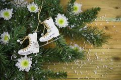 Christmas photography picture with tree branches and ice skating boots decoration and white winter flowers sprinkled with snow. Studio image on natural wood stock image
