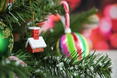 Christmas photography picture of tree branches and little red house with candy canes and red fairy lights in background. Christmas image of little wooden red Royalty Free Stock Images