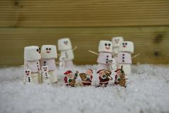 Christmas photography image made with marshmallows shaped into happy snowman with icing for the smiles and Santa Claus decorations Royalty Free Stock Photos