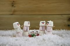 Christmas photography image made with marshmallows shaped into happy snowman with icing for the smiles and glass gift decorations Royalty Free Stock Photography