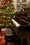Christmas Piano. Baby grand piano with Christmas tree & presents in background Royalty Free Stock Photo