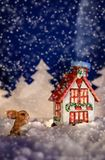 Christmas picture with the Bunny and cabin winter night in the s. Christmas fairy-tale picture of a Bunny next to the house on a winter night in the snow Royalty Free Stock Photos
