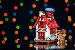 Christmas picture of a Bunny near the house on a background of colored lights. Christmas picture of a Bunny near the window of a house on the background of Stock Images