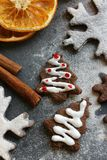 Christmas picture. Chocolate gingerbread Christmas trees and snowflakes sprinkled with flour on a dark background Stock Image