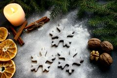 Christmas picture. Cookies in the form of snowflakes, floured, led candle lights, scattered nuts, cinnamon and orange slices. stock photography