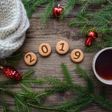 Christmas picture with the number 2019 on round cookies with a cup of tea on a wooden background. New Year picture with Christmas tree branches and the number royalty free stock photo