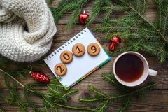 Christmas picture with the number 2019 on round cookies with a cup of tea on a wooden background. New Year picture with Christmas tree branches and the number stock image