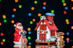 Christmas picture with Santa and a Bunny near the house on a background of colored lights. Christmas picture with Santa and a Bunny near a small beautiful house Royalty Free Stock Image