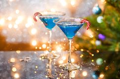 Christmas picture of two wine glasses with blue cocktail, caramel sticks and garland Stock Photos