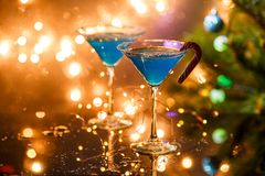 Christmas picture of two wine glasses with blue cocktail and garland. On blurred blue New Year`s background Stock Photo