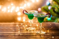 Christmas picture of two wine glasses with green cocktail, caramel sticks and garland Royalty Free Stock Photography