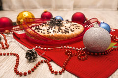 Christmas pie decorated with holly twig and balls in festive set Stock Photos
