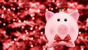 Christmas piggy bank ball with ribbon bow on red blurred lights Stock Images