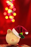 Christmas Piggy bank Santa with festive bokeh Stock Photos