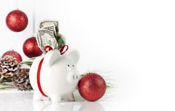 Christmas Piggy Bank. A white piggy bank tied with red ribbon and US currency in top slot, christmas ornaments along side and blurred in background. A concept Stock Photos