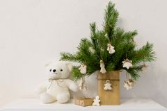 Christmas pine branch in vase with homemade cookies white bear. decor in Scandinavian style, white background. Christmas pine branch in vase with homemade royalty free stock image