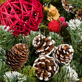 Christmas Pine Cones. Close-up of a Christmas still-life in the studio with a green wreath, red cane ball, glittery berries in red and gold and frosted pine Stock Image