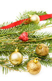 Christmas pine tree branch and decorations. Celebrating Christmas with traditional pine tree branch and golden baubles. Isolated on white background Stock Photos