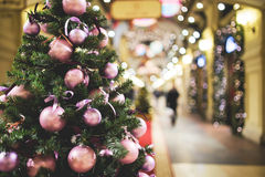 Christmas pine-tree decorated with balls. Christmas pine tree decorated with purple balls standing in lobby of store, toned photo Stock Image