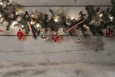 Christmas pine tree garland with red baubles, candy canes and ornaments, hanging on old wooden board background Royalty Free Stock Photo