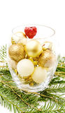 Christmas pine tree and golden baubles. Celebrating Christmas with bowl of golden baubles and red heart on traditional pine tree branch. Isolated on white stock photos
