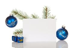 Christmas pine twig, two toys-balls, small gifts, and blank card isolated on white Royalty Free Stock Photography