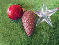 Christmas- pinecone decorated with stars and red glowing ball on green fluffy background Stock Photos