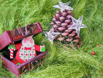 Christmas- pinecone decorated with stars and small wooden chest with funny Santa Claus inside on gr een fluffy background Stock Photography