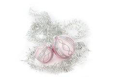 Christmas in pink. Two pink christmas ornaments, a silver festoon, and a white background Royalty Free Stock Photos