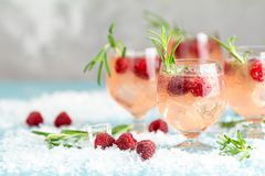 Christmas pink drink raspberry with rosemary and ice. Glasses with cold and healthy beverage. Welcome drink. Holiday, juice, winter, summer, water, food, fruit stock photos