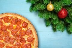 Christmas Pizza pepperoni with fir branches, new year toy ball on blue wooden background. Winter holiday decoration top view.  stock photography