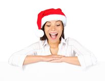 Christmas placard sign woman. Beautiful mixed asian / caucasian woman leaning over blank billboard sign looking down being excited and surprised. Isolated on Stock Photo