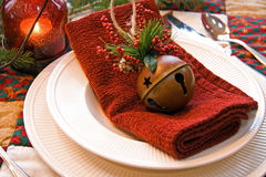 Christmas Place Setting. This is a shot of a Christmas place setting with ivory plate and bowl, red fabric napkin, bell Christmas ornament and a red lit bubble stock photography