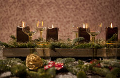 Christmas place setting with candles. Are wine glasses on the table, pine tree branches are adorned with decorative snow Royalty Free Stock Image