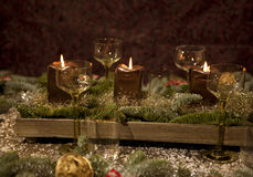 Christmas place setting. With candles, are wine glasses on the table, pine tree branches are adorned with decorative snow Royalty Free Stock Images