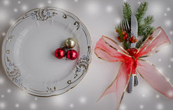 Christmas place setting, plate, knive and fork. Christmas table place setting with christmas pine branches and plate, knife, fork and ribbon. Christmas holidays Stock Image