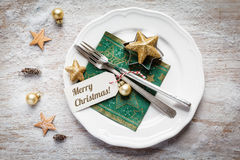 Christmas place setting, plate, napkin, knive and fork. With flour on wooden background Royalty Free Stock Images