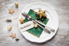 Christmas place setting, plate, napkin, knive and fork. With sign reading Invitation Stock Photos