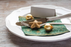Christmas place setting, plate with napkin, knive and fork. On wooden background Royalty Free Stock Photos