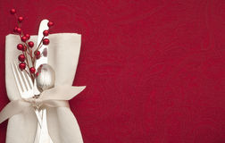 Christmas Place Setting with Sterling Silverware in White Napkin and Ribbon on Red Background with Copy space or Room for Your Tex. Horizontal of red table cloth Stock Photos