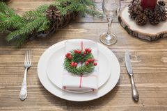 Christmas place setting with white dishware, silverware and decorations on wooden board. Christmas wreath as decor. Christmas place setting with vintage royalty free stock photos