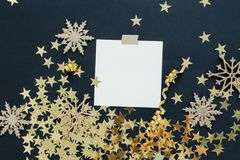 Christmas planning concept mock up. Note on black background with washi tape, gold stars confetti, serpentine and glitter snowflak Royalty Free Stock Photography