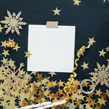 Christmas planning concept mock up. Note on black background with washi tape, gold stars confetti, serpentine and glitter snowflak Stock Image