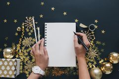 Christmas planning concept mock up. Women hands with wach writing on notebook on black background washi tape, gold stars confetti,. Christmas planning concept Royalty Free Stock Images