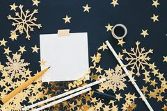 Christmas planning concept mock up. Note on black background with washi tape, gold stars confetti, serpentine, pen and glitter sno Royalty Free Stock Images